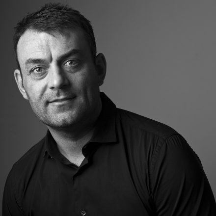 Black and White Commercial Portrait of Man in Black Shirt with Short Hair © Paul Worpole Photography