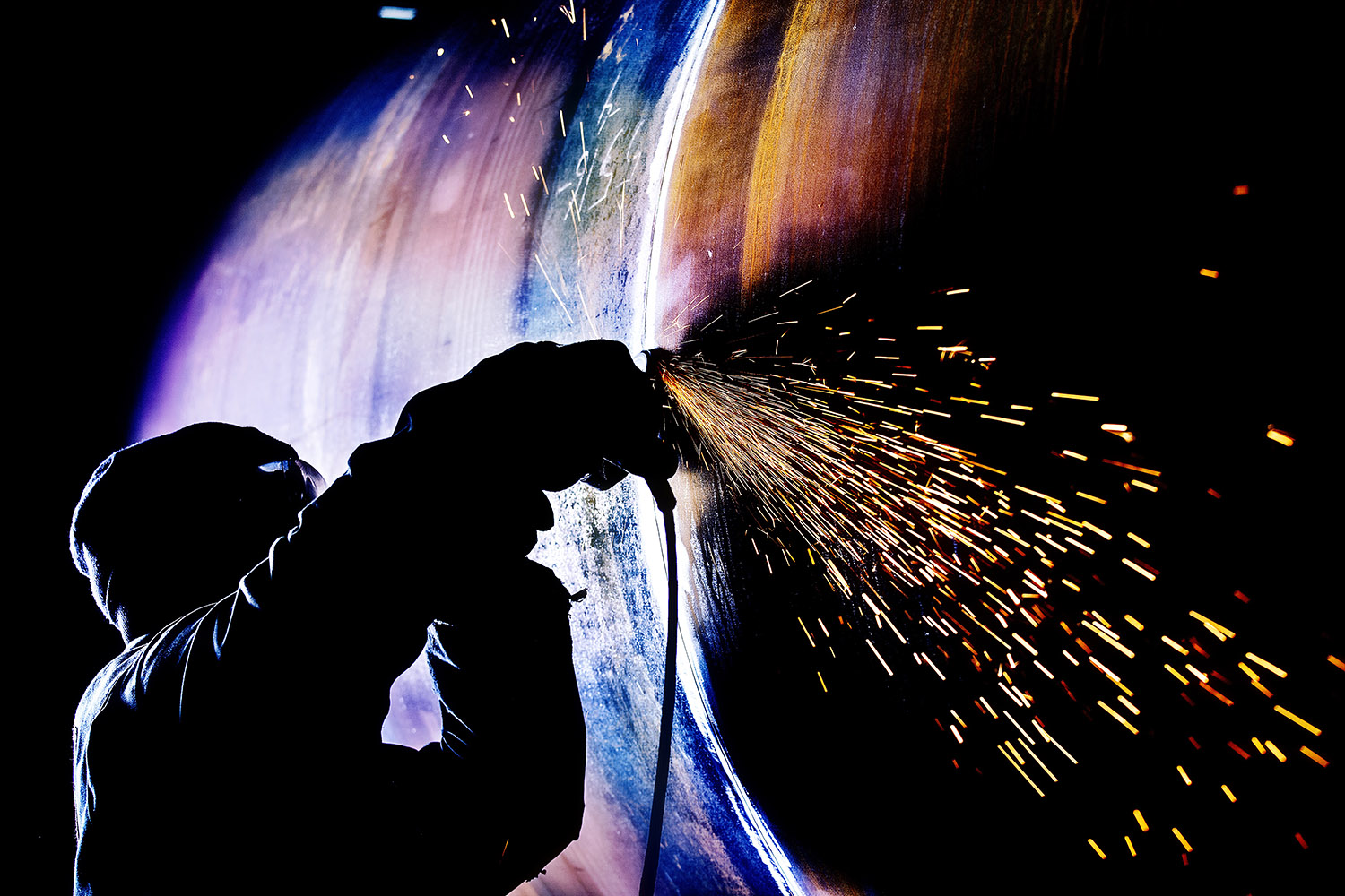 Industrial Commercial silhouette Portrait of man with sparks flying from grinding disc © Paul Worpole Photography
