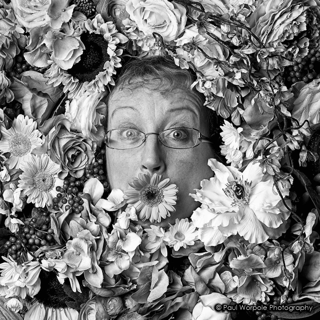 Black and White Portrait of Bridgette the Florist Woman surrounded with Flowers with flower in Mouth © Paul Worpole Photography