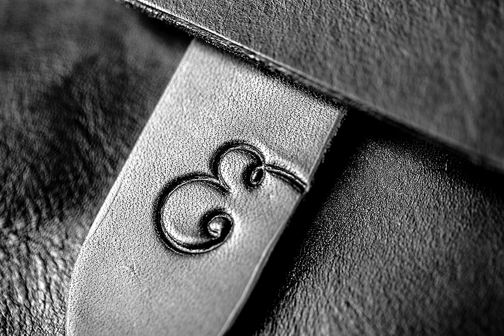 Leather Handbag Detail Product Photography  black and white with a script E embossed on it © Paul Worpole Photography