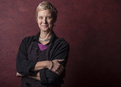 Corporate Portrait of a Woman Folded arms against a Red speckled Backdrop © Paul Worpole Photography