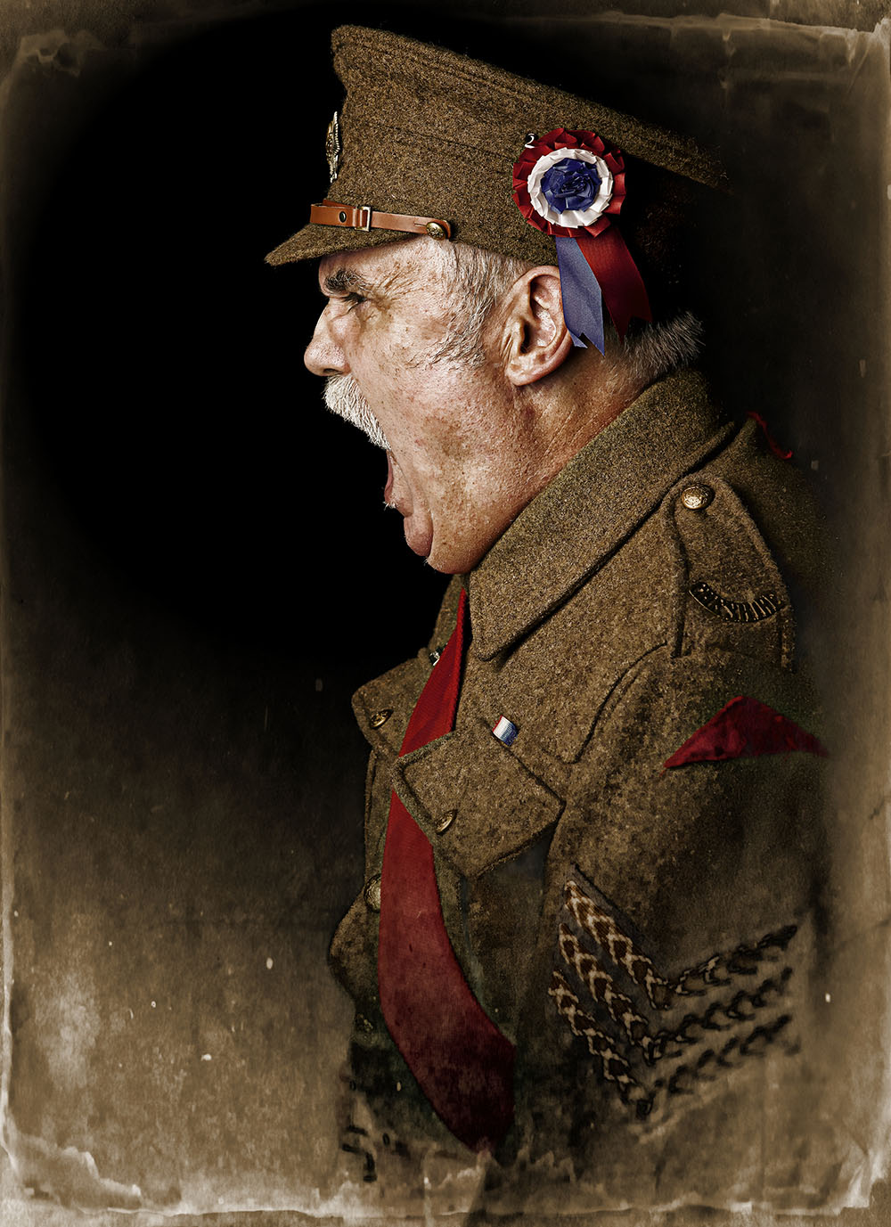 Sepia and colour profile portrait of World War One Sergeant shoting orders. Edges of frame faded by Paul Worpole
