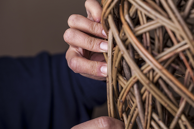 Hands of a woman weaving willow