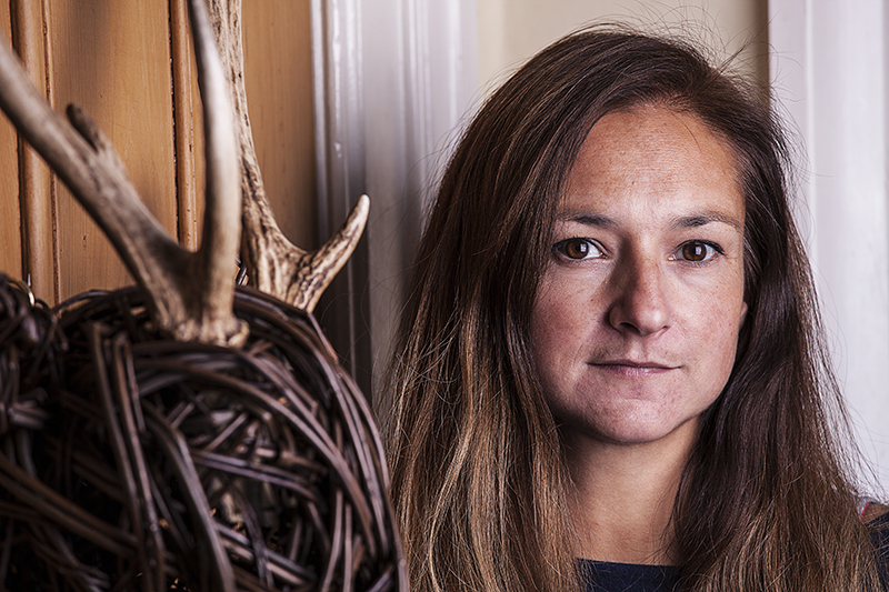 Portrait of woman with willow deer head on door