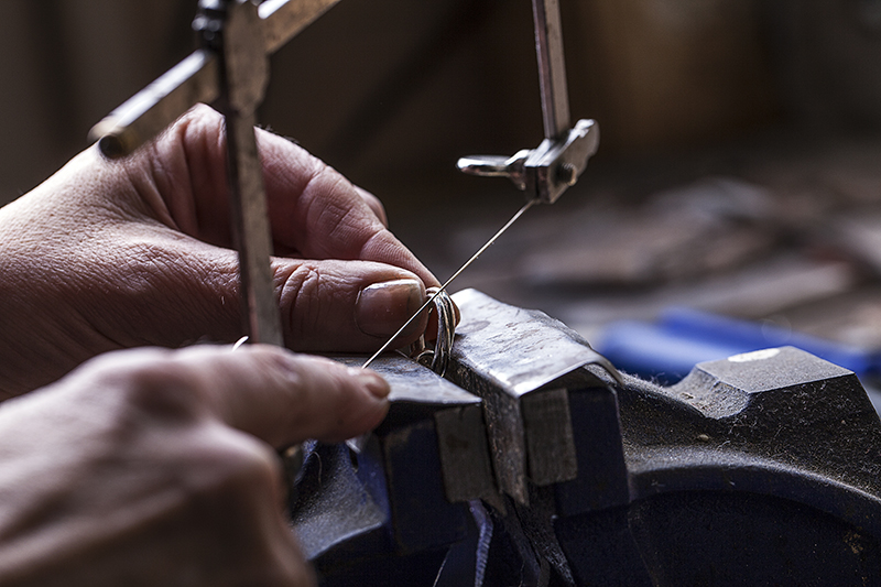 Silver Jeweller working with fret saw