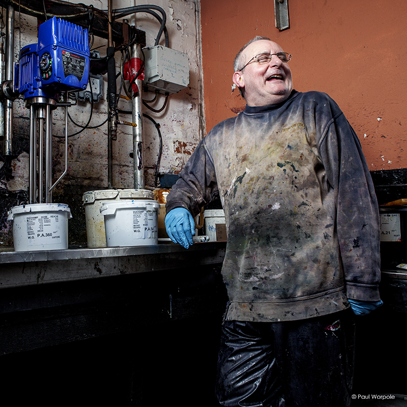 Environmental Portrait Man mixing dye laughing covered in paint splatters© Paul WorpolePhotography