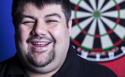 Portrait of man smiling with beard in front of a Unicorn dart board