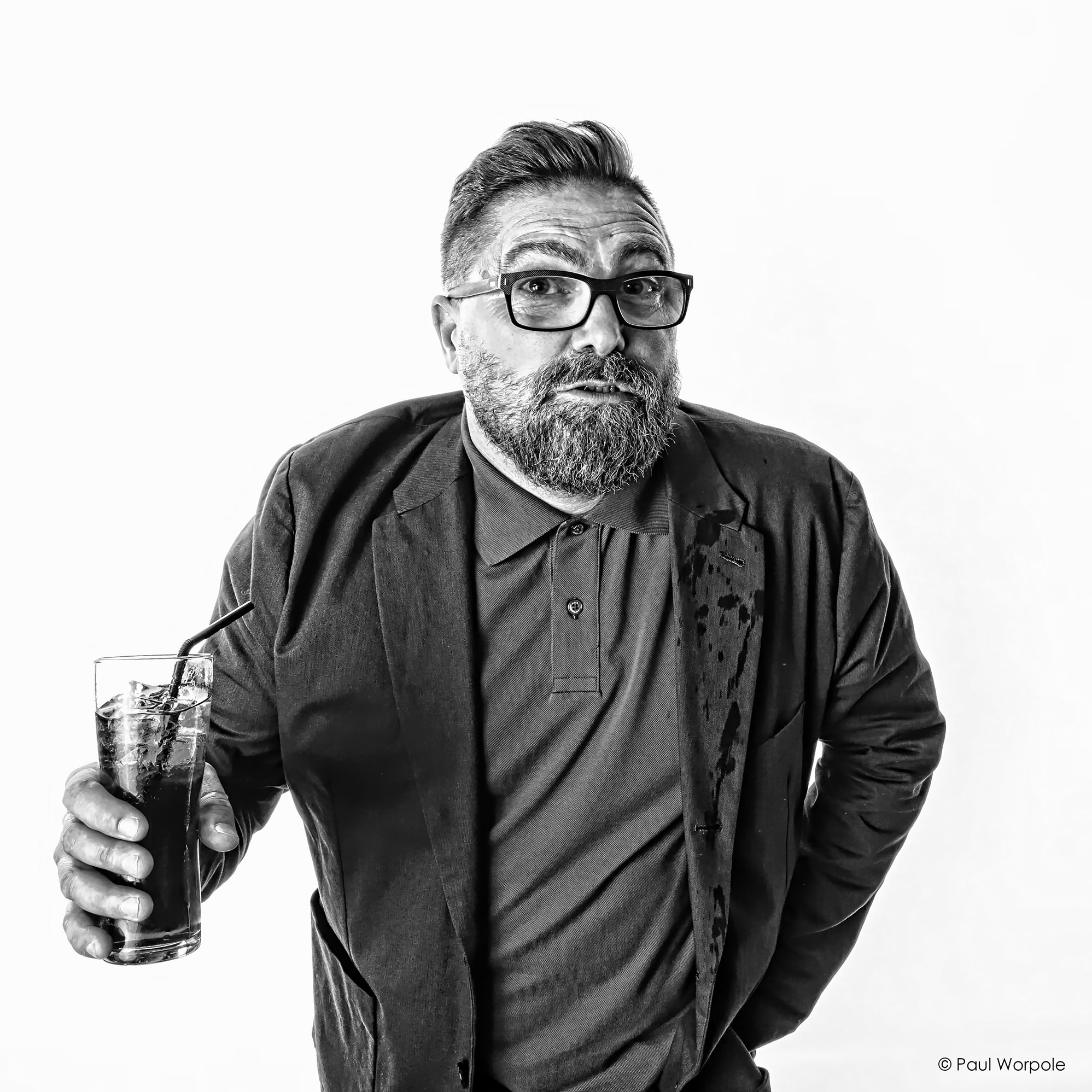 Black and white portrait of a man with a beard and glasses holding a drink with a straw © Paul Worpole