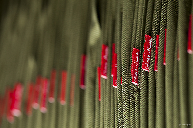 Close up detail shot of Oliver Harvey tab on olive green apron © Paul Worpole