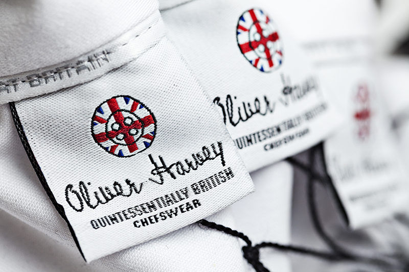 Advertsing Photograph Close up shot of clothing label saying Oliver Harvey and Quintessentially British Chefswear and a round log with Union flag on © Paul Worpole Photography