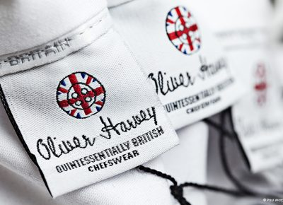 Commercial Photograph Close up shot of clothing label saying Oliver Harvey and Quintessentially British Chefswear and a round log with Union flag on © Paul Worpole Photography