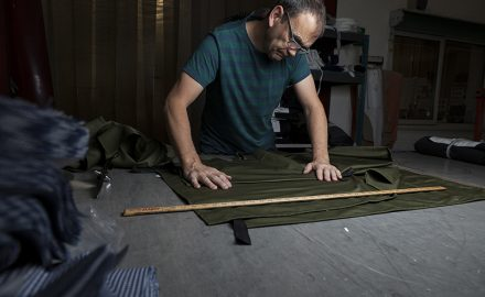 Commercial portrait of Man Tailor looking down at green cloth estimating cuts with large wooden ruler ©Paul Worpole Photography