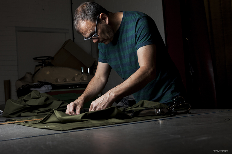 Tailor measuring cloth on cutting table © Paul Worpole