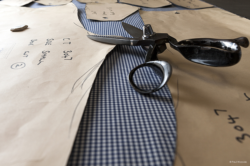 Tailors shears on blue gingham cloth with patterns for chefs trousers
