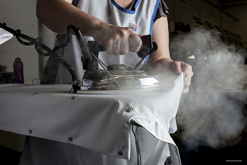 Woman ironing a Chefs jacket with steam coming out of iron©Paul Worpole