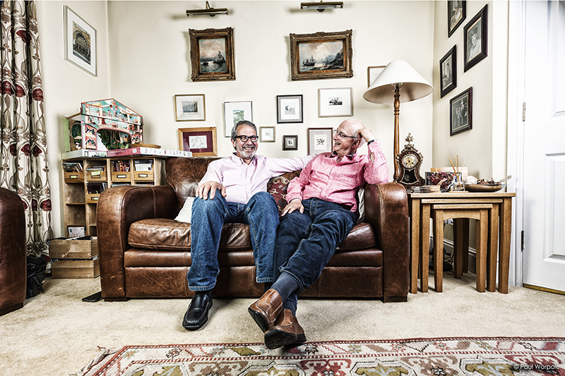 Commercial Portrait of Two Men Sitting on Leather Sofa Laughing in a Living Room with Pictures on Wall for Clients Greystone Financial © Paul Worpole Photography