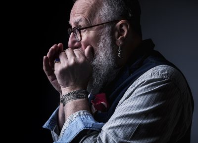 Advertising portrait of Man playing harmonica with beard and glasses © Paul Worpole Photography