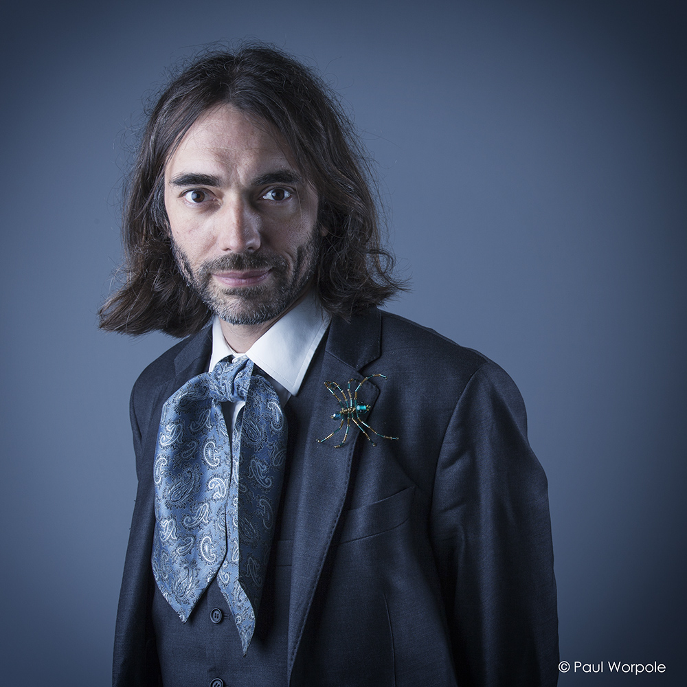 Commercial Headshot of Man with Long hair and Cravat and Jewellary Spider on Lapel of suit © Paul Worpole Photography