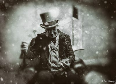 Black and White Corporate Advertising Portrait of a Man in Top Hat and Sunglasses Holding a Pocket Watch with Snow Falling For Client Greystone Financial Services © Paul Worpole Photography