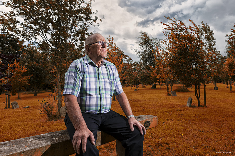 Man sitting in graveyard Autumn colours © Paul Worpole