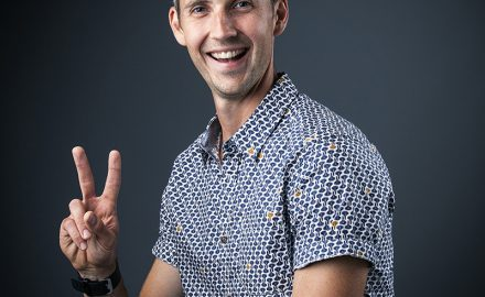 Professional Corporate Headshot of Man in short sleeve shirt smiling showing Victory sign with fingers © Paul Worpole Photography