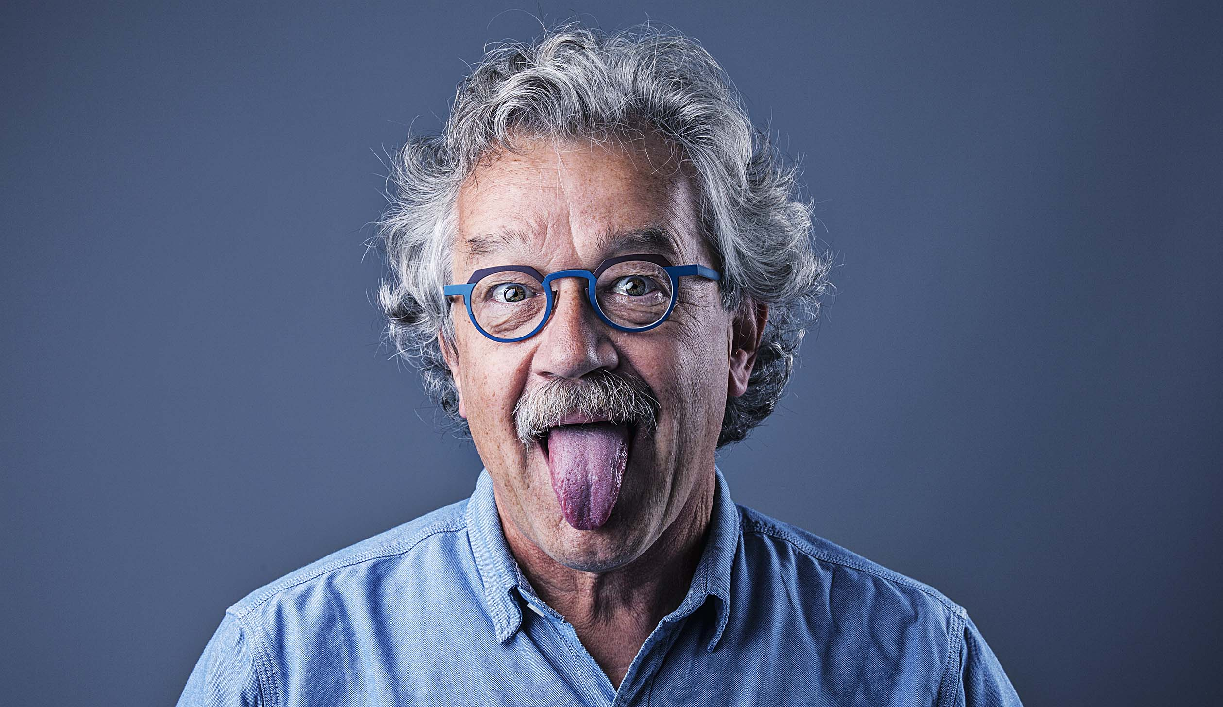 Commercial Portrait Photography of Man Sticking Out Tongue with glasses on in blue denim shirt © Paul Worpole Photography