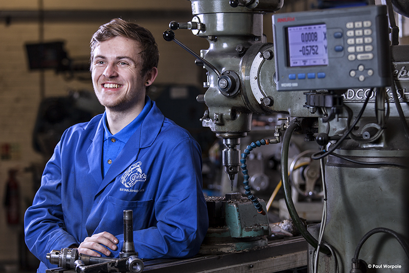 technicians make it happen portrait of technician leaning against metal drilling machine in blue overalls at