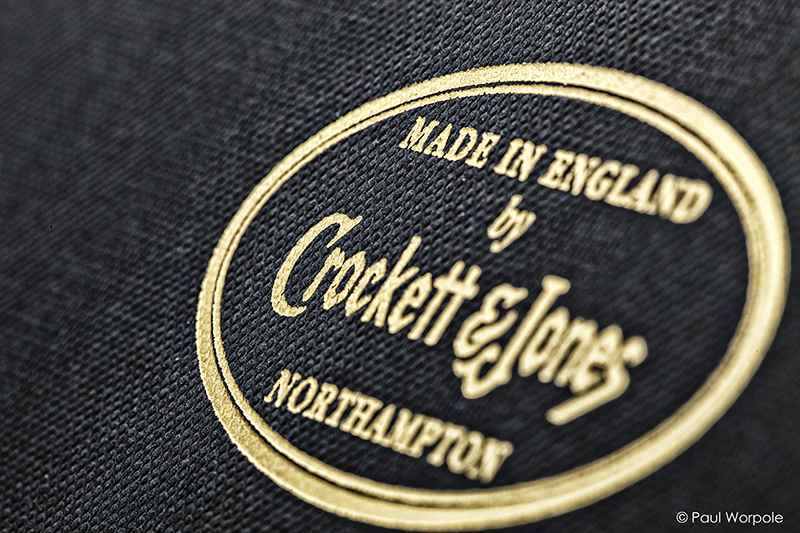 Crockett & Jones Northampton Shoemaker Close Up Detail of Dark Blue Shoebox Texture and Gold Crockett and Jones Logo © Paul Worpole Photography
