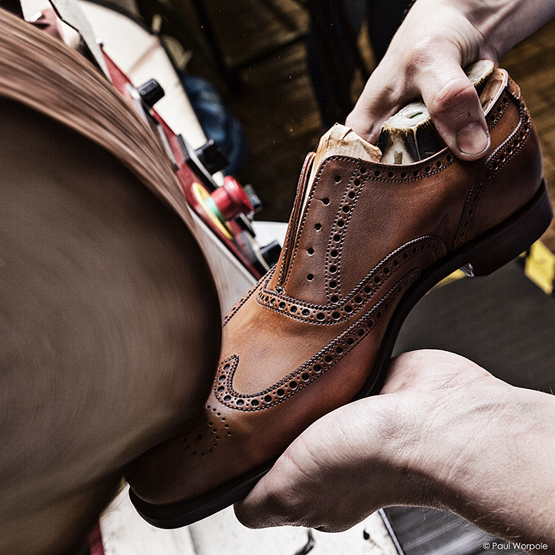 Crockett and Jones Northampton Shoemaker Man Hands Shown Polishing Brown Brogues on a Polishing Wheel © Paul Worpole Photography