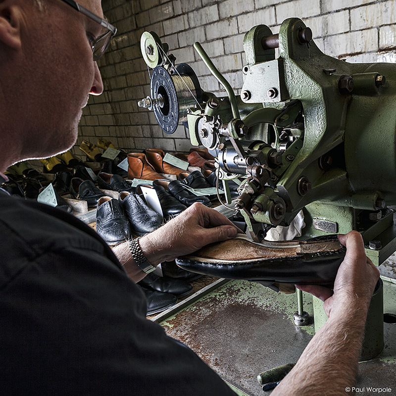 Crockett and Jones Shoemakers Northampton Close Up Detail of Man Repairing Shoes with New Sole on Machine © Paul Worpole Photography