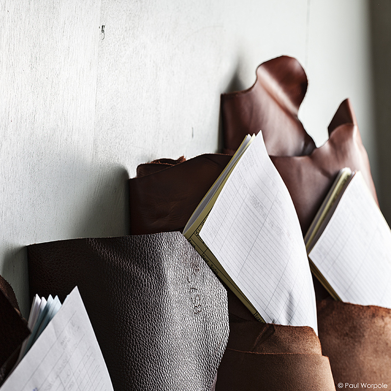 Crockett & Jones Shoemakers Northampton Close Up of Rolls of Leather Leaning Against a Wall with Yellow Paper Orders Attached © Paul Worpole Photography