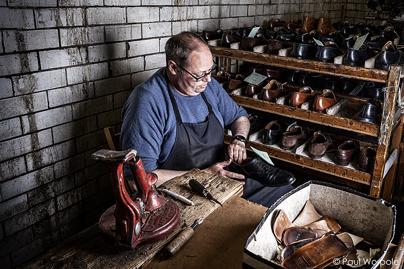 Crockett and Jones Shoemakers Northampton Man Removing Liners of Black Cap Oxford Shoe for Complete Renewal Repair © Paul Worpole Photography
