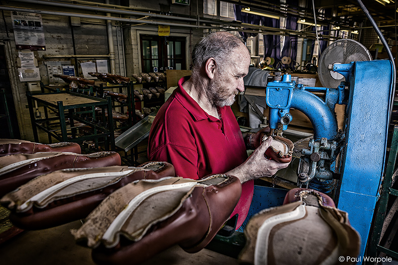 Crockett and Jones Shoemakers Northampton Man in Red Polo Shirt Sewing Sole onto Leather Uppers with a Machine © Paul Worpole Photography