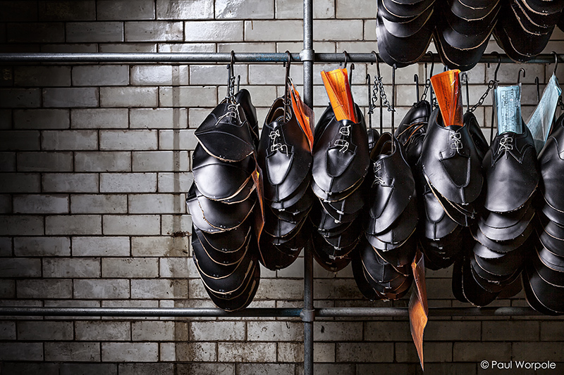 Crockett & Jones Shoemakers Northampton Unsold Black Shoe Leather Hanging On Metal Bars in Basement with White Tiles © Paul Worpole Photography