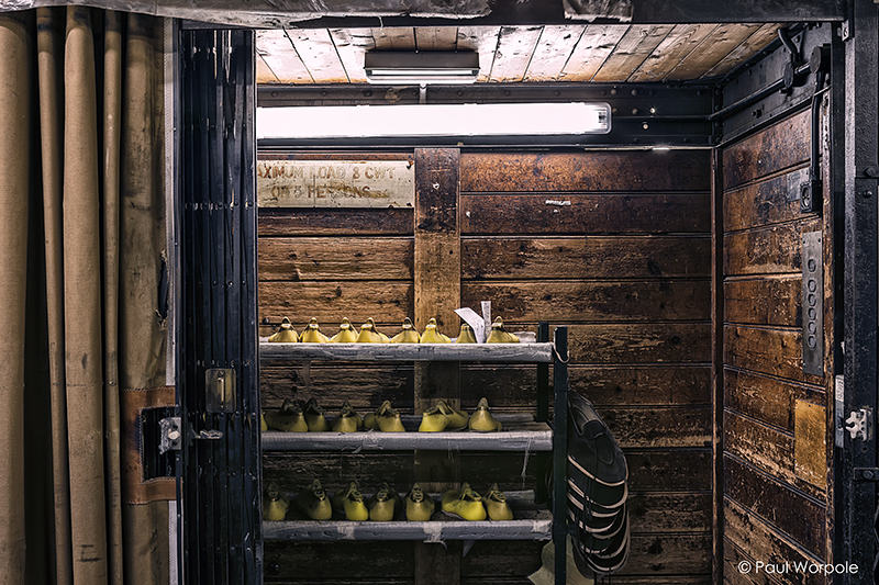 Crockett & Jones Shoemakers Northampton Wood Lined Lift in Basement Moving a Rack of Yellow Lasts to the Next Floor © Paul Worpole Photography