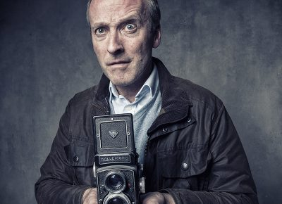 Portrait of Man with Rolleicord Twin Lens Reflex Camera in Barbour Coat © Paul Worpole Photography