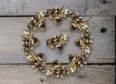 Product Photography of Gold Bee Arrings in a circle on weathered wood © Paul Worpole Photography