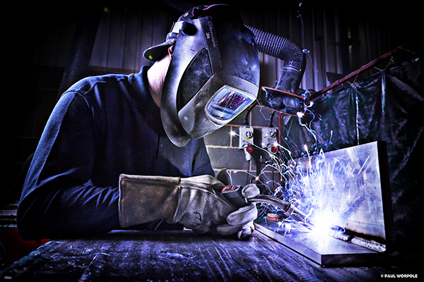 Industrial Welding PhotographyMan in welding mask welding aluminium with sparks flying purple filter © Paul Worpole Photography