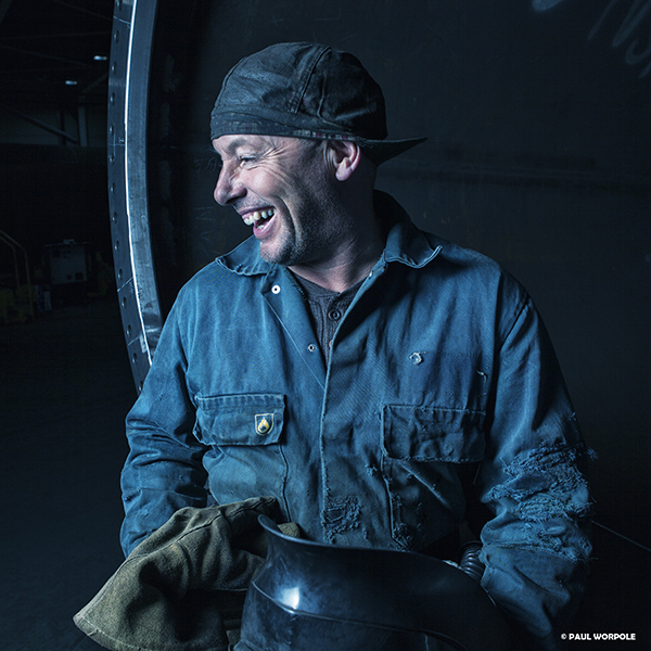Welding Photography Industrial Man laughing with welders cap on holding helmet and gloves sitting on a steel pipe © Paul Worpole Photography