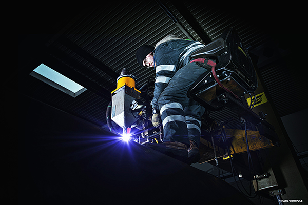 Welding Photography Industrial Man sitting 10 feet in the air on top of a welding machine welding steel tube © Paul Worpole Photography