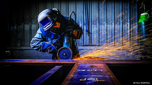 Industrial photograph of fabricator with protective helmet grinding steel in a workshop sparks flying from the grinding machine © Paul Worpole Photography