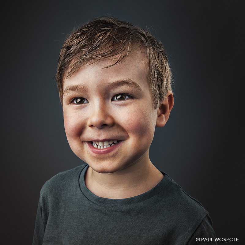 Staff Headshot Photography with our mobile studio in your offices Portrait of four year old boy smiling © Paul Worpole Photography