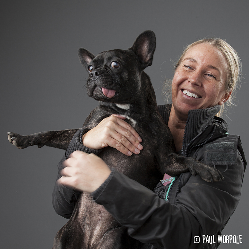 Blonde woman holding a black pug with its tongue out © Paul Worpole Photography