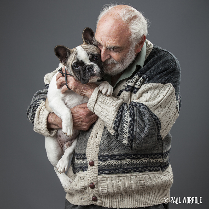 Man in cardigan holding a french bulldog © Paul Worpole Photography