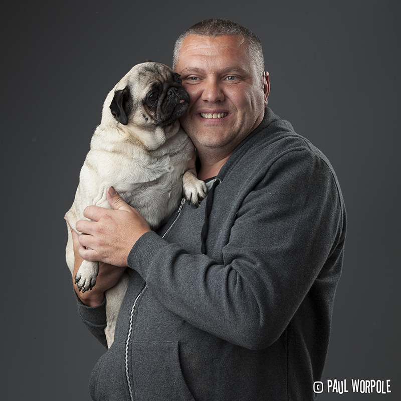 Man in dark grey hoodie with pug © Paul Worpole Photography