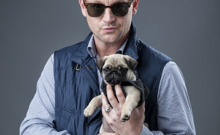 Man in flat cap and sunglasses holding a pug puppy © Paul Worpole Photography