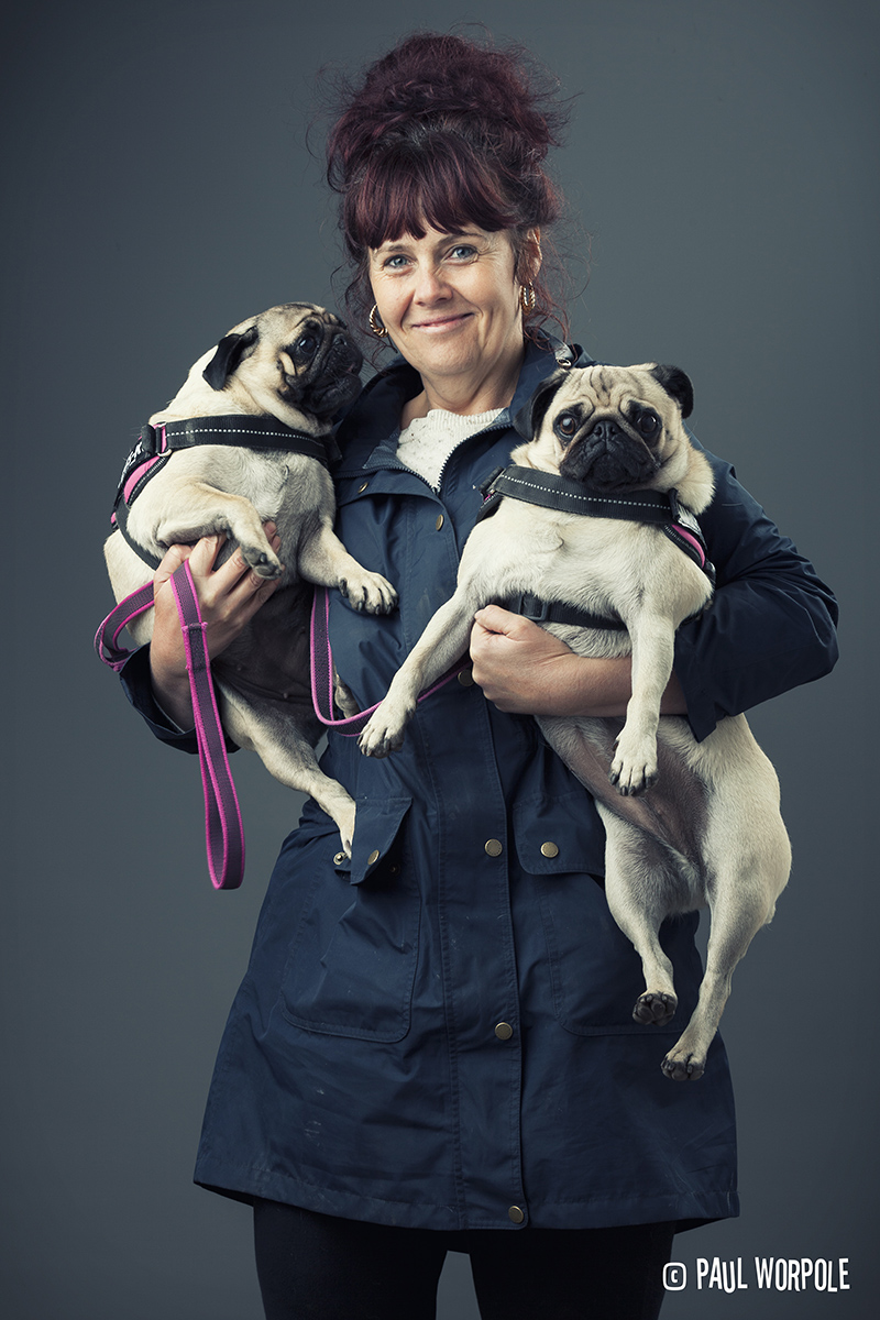 Woman holding two pugs with big hair © Paul Worpole Photography