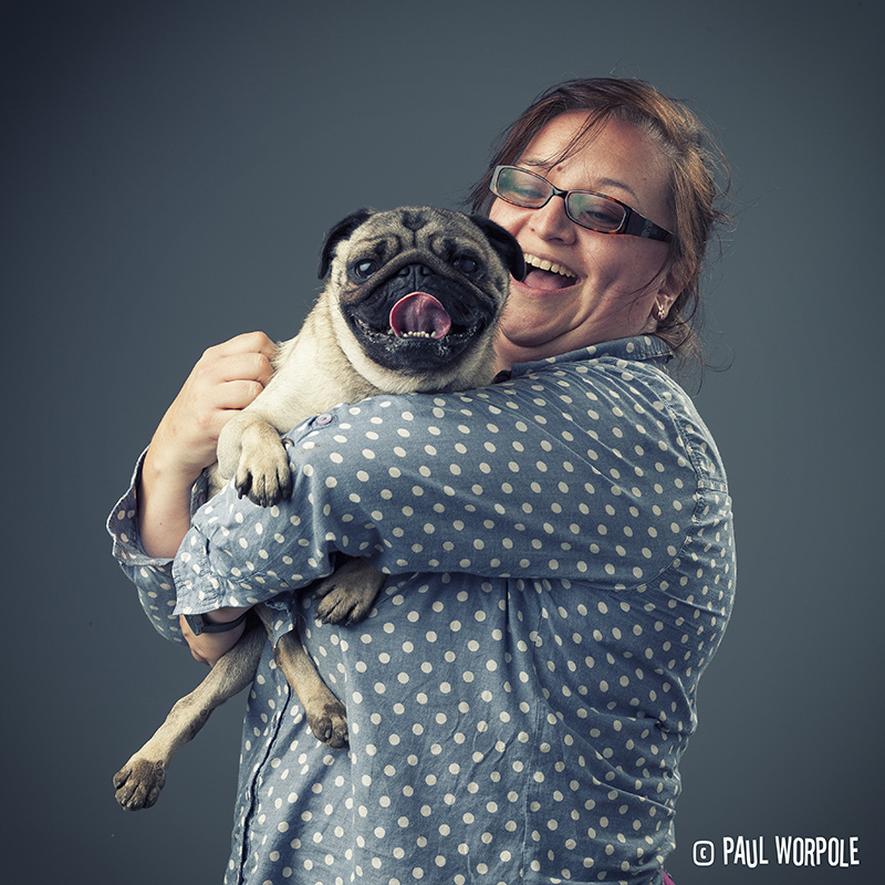 Woman in spotty shirt laughing holding a pug© Paul Worpole