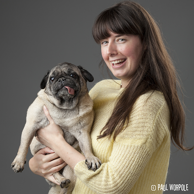 Woman in yellow jumper holding a pug with tongue out © Paul Worpole Photography