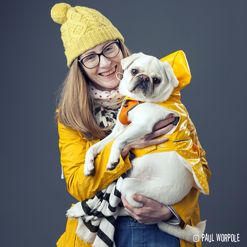 Woman in yellow mackintosh and bobble hat with a pug© Paul Worpole Photography